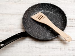 Frying pan with non-stick ceramic coating and spatula on a white wooden background. Cooking without sticking or oil.